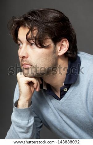 Dark-haired man thinking - stock photo
