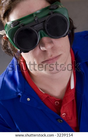 Dark haired man with blue overall and welding goggles - stock photo