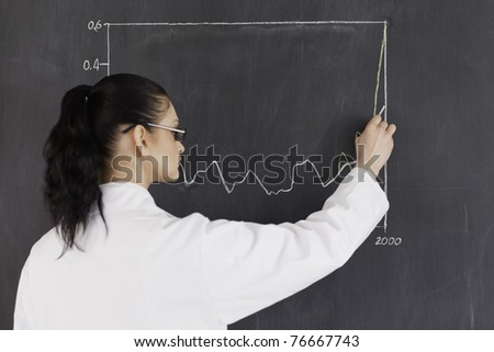 Dark-haired scientist drawing charts on the blackboard in a lab - stock photo