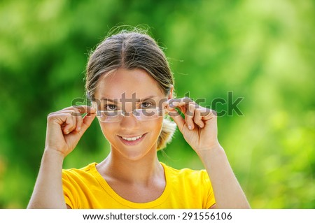 Dark-haired smiling beautiful young woman in yellow blouse and glasses, against green of summer park. - stock photo