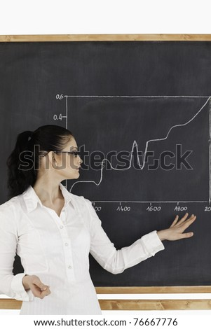 Dark-haired teacher explaining charts to students in a classroom - stock photo