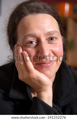 dark haired woman is smiling in to the camera - stock photo