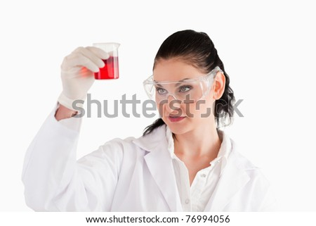 Dark-haired woman looking at a red beaker in a lab