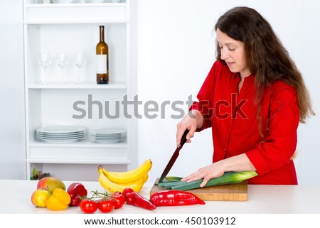 dark haired woman with red shirt in the kitchen