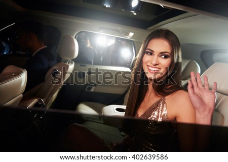 Dark haired young woman waving from the back of a limo - stock photo