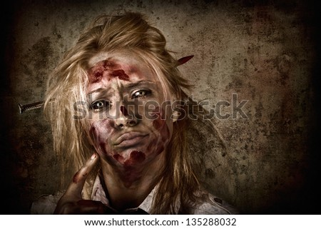 Dark horror portrait of a sinister female zombie businesswoman thinking up a sharp idea with nail through head on grunge background - stock photo