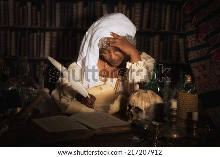 Dark image of a vintage alchemist writing in her books - stock photo