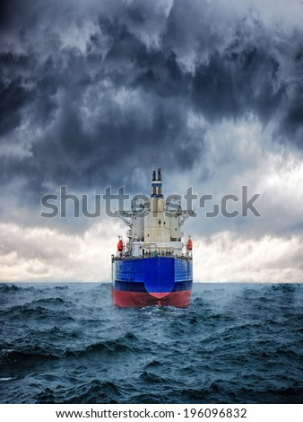 Dark image of big cargo ship in strong storm. - stock photo