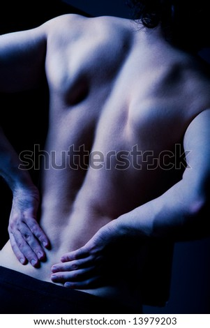 Dark image of human back pain with hands on it - stock photo
