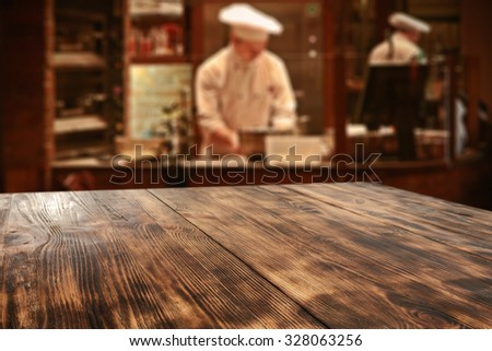 dark interior of restaurant with kitchen chef and board of wood  - stock photo