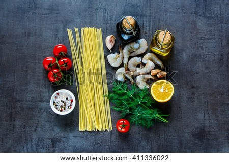 Dark kitchen table and ingredients for pasta with seafood. Shrimps, spaghetti, dill, garlic, spices and cherry-tomatoes over grunge backdrop from above. - stock photo
