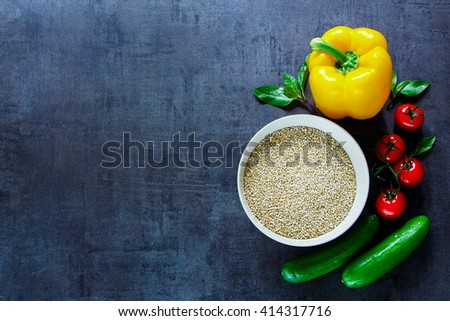 Dark kitchen table with bowl of healthy white quinoa seeds and fresh organic vegetables, top view, place for text. Healthy Eating, Diet, Vegetarian or Cooking concept - stock photo