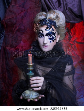 Dark Lady. Portrait of young woman in black posing with candle. - stock photo