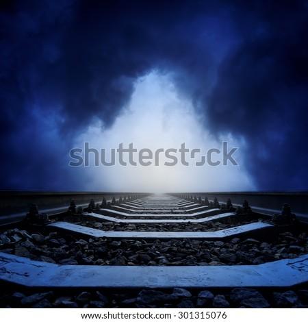 dark light in dramatic sky over railway - stock photo