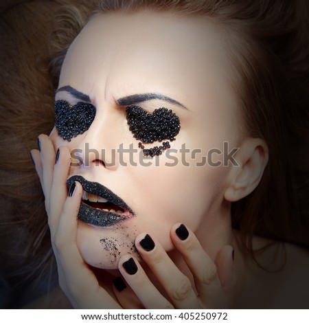 Dark lips makeup & nails polish. Close-up portrait of female caucasian young blonde model with black lipstick, fingernails and black caviar as a heart symbol on eyes. Studio portrait. Toned