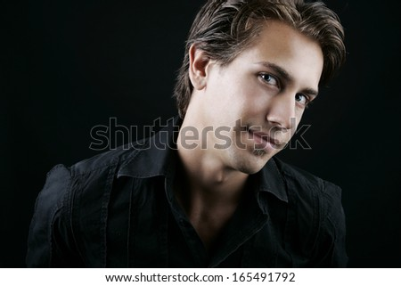 Dark moody close up portrait of the face of a handsome young man glancing sideways at the camera
