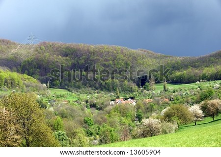 Dark moody clouds over a sunny and green landscape
