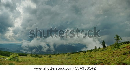 Dark mountain landscape with dramatic sky before the storm and low spruce on foreground. Black stormy sky in the rain in the mountains. Nature force background - huge rain in mountains panoramic view - stock photo