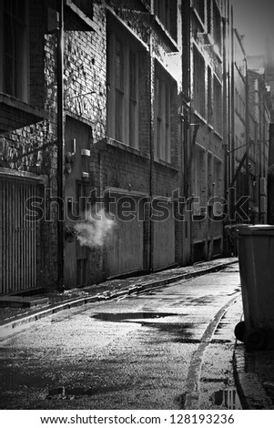 Dark mysterious alleyway on a rainy day - stock photo