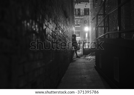 dark narrow alleyway with person posing by wall, with street light illuminating the scene.  - stock photo
