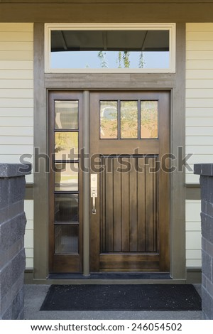 Dark Natural Wood Front Door with Panels and Window Panes Behind Slate Colored Brick Wall - stock photo