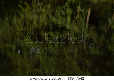 dark pattern of the blurry green reflection on the water surface