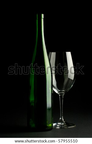 Dark photo of a green wine bottle and a wine glass - stock photo