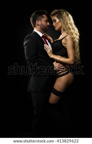 Dark photo of a young couple in sensual lingerie and suit