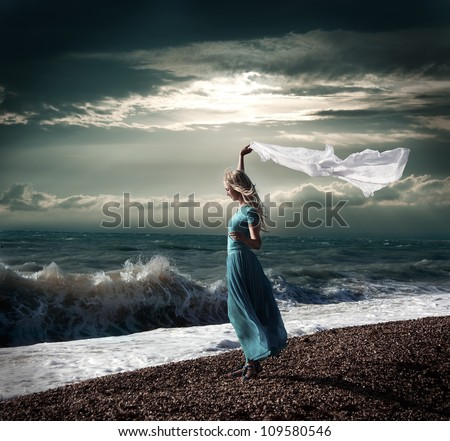 Dark Photo of Blonde Woman with White Scarf at Stormy Sea - stock photo