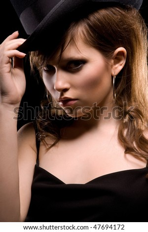dark picture of woman in black dress and top hat - stock photo