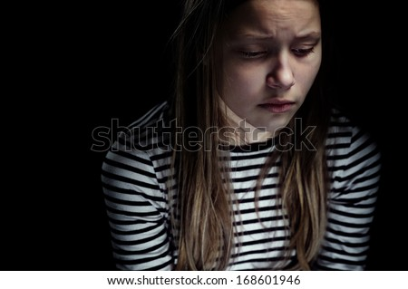 Dark portrait of a depressed teen girl, studio shot - stock photo
