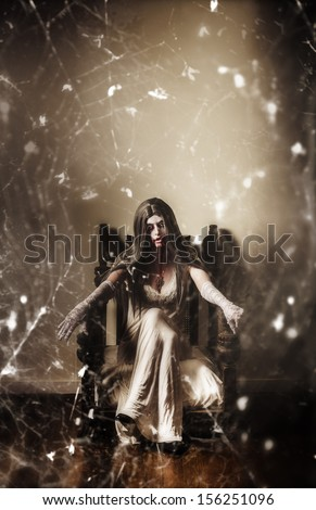 Dark portrait of a possessed demon woman  seated in haunted house in vintage fashion with spiderweb. Devil is in the details - stock photo