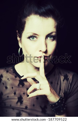 dark portrait of a woman with finger on lips - stock photo