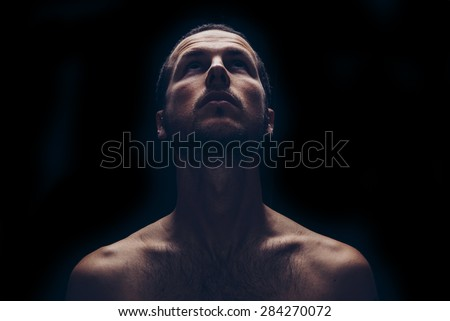 dark portrait of an handsome man looking up - stock photo