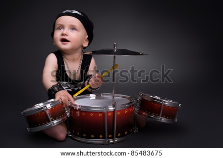 dark portrait of  Beautiful boy playing the drums on a black background - stock photo