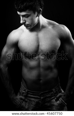 Dark portrait of guy with muscular body - stock photo