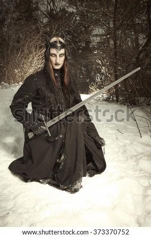 Dark princess in winter forest - stock photo