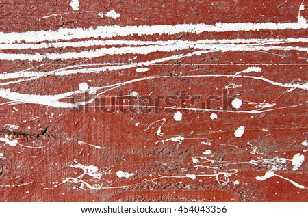 Dark red, maroon concrete wall with white paint drips, drops and stains. Abstract background, rough grunge texture, dirty and messy old urban wall surface. - stock photo