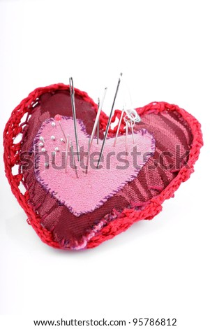 Dark red pillow heart with thread and needle as symbol of unhappy love, suffering and pain