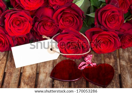 dark red roses with two hearts and tag  on wooden  table - stock photo