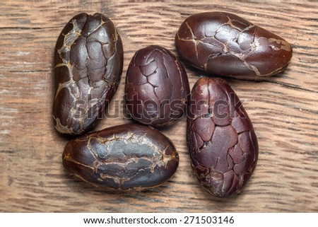 dark roasted and peeled cocoa beans extreme closeup on wood background in Honduras  - stock photo
