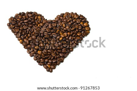 Dark roasted coffee beans in the shape of a heart with limited depth of field, isolated on white.