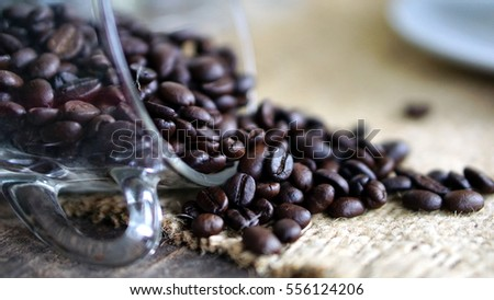Dark roasted coffee beans put on a wood table with A cup of coffee.