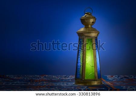 Dark Room With Ramadan Lantern over Ramadan Fabric - stock photo