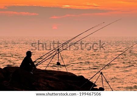 Dark silhouette of a fisherman on sunset sky and sea background