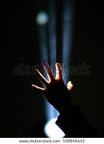dark silhouette of human male hand with fingers in spotlight or backlight light with gesture on black background with dramatic projector shine ray or beam