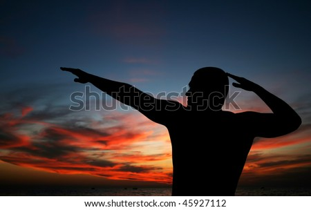 dark silhouette of young man on the beach - stock photo