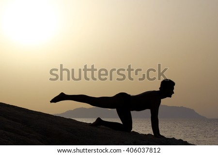 dark silhouette of young sporty man doing yoga exercises at sunrise on the beach