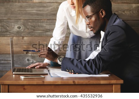 Dark-skinned entrepreneur sitting at table and pointing at computer screen to find solution with his Caucasian personal assistant. Female colleague stands listening to business partner attentively. - stock photo