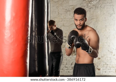 Dark-skinned guy with naked torso in boxing gloves, boxing in gym decorated in loft style, boxing guy, black punching bags in the background - stock photo